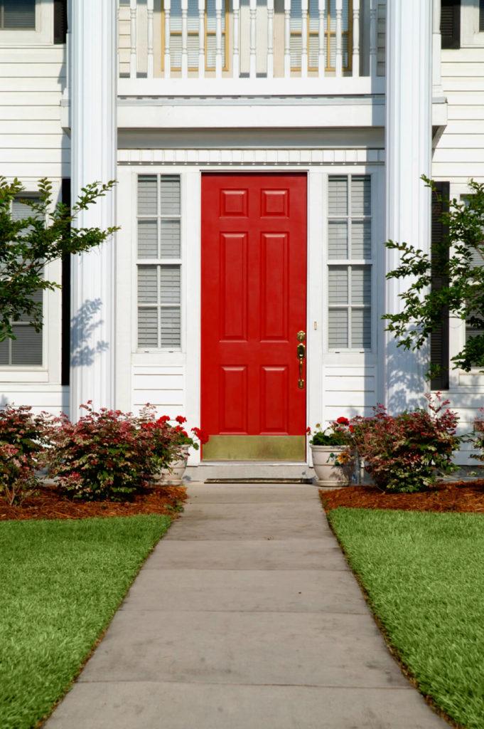 The entry, a six-paneled door, is red and has a bronze kick-plate. On both sides are sidelights with inside blinds for privacy. There are balcony railings above the red door supported by two white pillars. The door is accessorized by a concrete pathway, green grasses, and multi-colored flowering plants.
