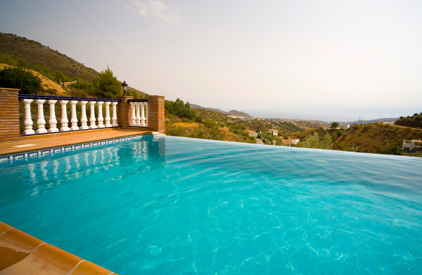 This Tuscan-style patio has a deep blue infinity pool on the edge of the hill, providing a lovely view of the quaint countryside and the water beyond.