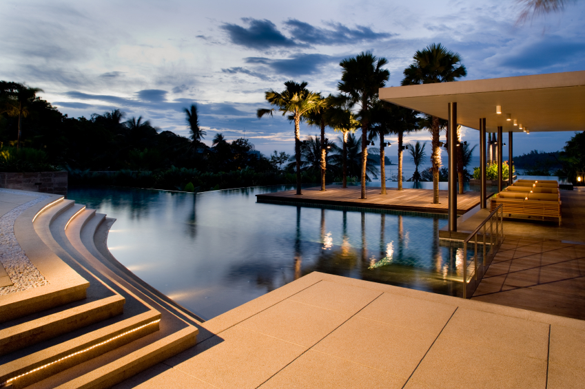This large patio and pool complex has a complicated layout. Part of the patio is in limestone tile, and has lighted steps. The lower part of the patio has plenty of seating beneath an extended cover, and is built to resemble a dock. The middle wooden platform looks like it's floating, but is actually built around already existing palm trees. The infinity pool loops around all of these obstacles for a very natural look.