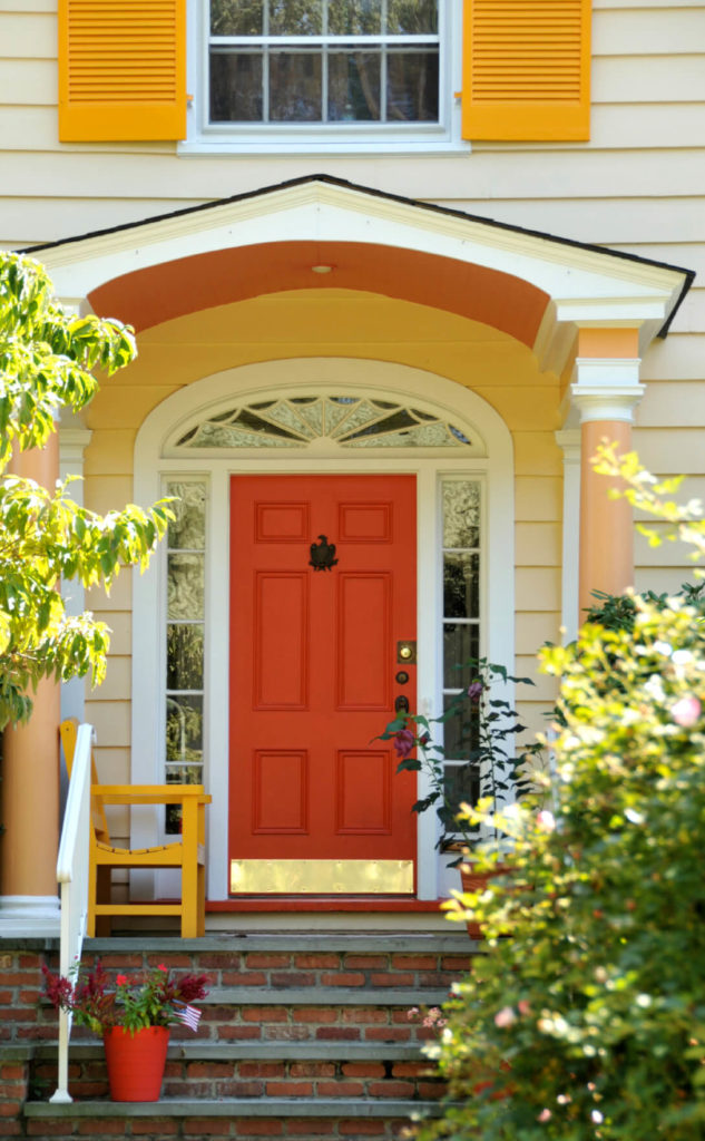 This front door and entryway has six panels with a gold metallic kick plate. The door has barn red coatings and is accessorized with a black eagle design door knocker made of cast iron, and black handle and locks. The arch-shaped door has multi-paneled sidelights and transom of clear and decorative glasses. A typically designed cottage door, it is supported by white casting and framing fixed to an ivory wall. The door ceiling is supported by beige-coated columns