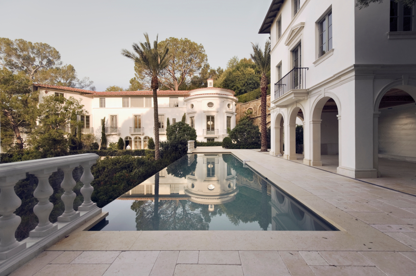 An infinity pool in a beautiful palace-like resort home with classical architectural details.