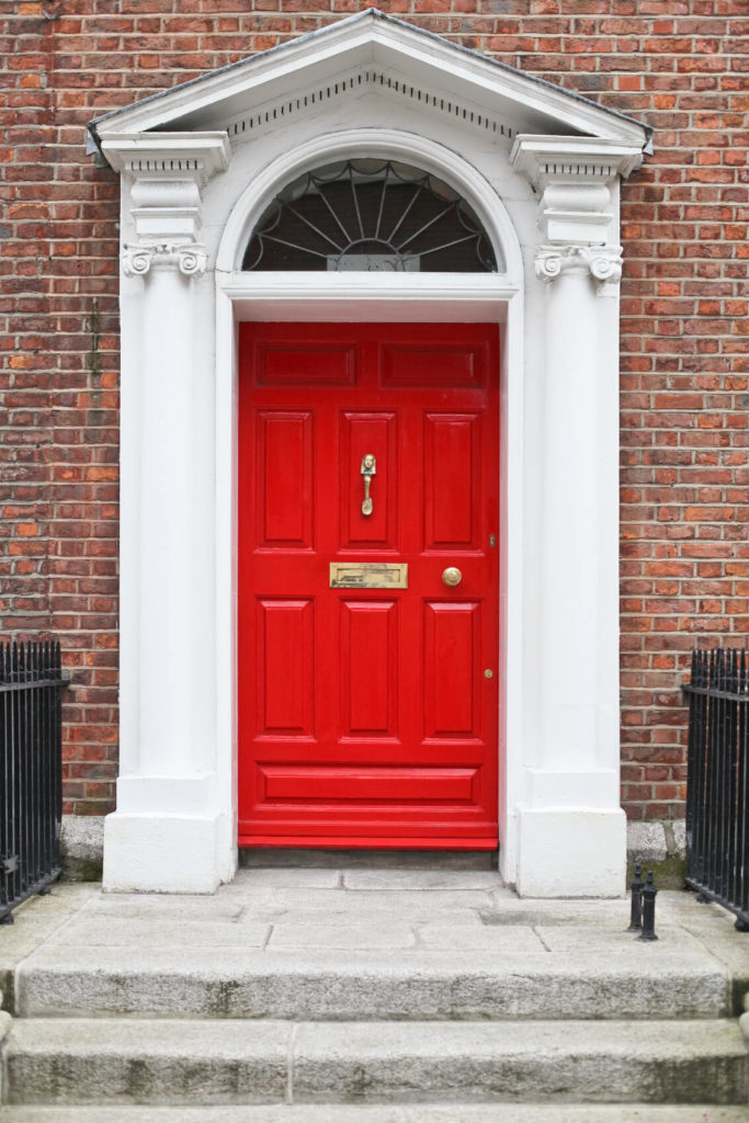A white door frame with an arched top and a half-circle transom help this red door stand out from the more muted shade of the bricks and light gray stone steps.