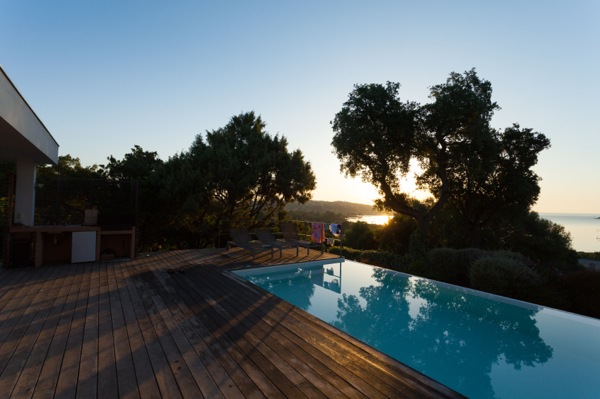 The simple wooden decking surrounding this pool on three sides keeps the attention on the pool and the lovely sunset.