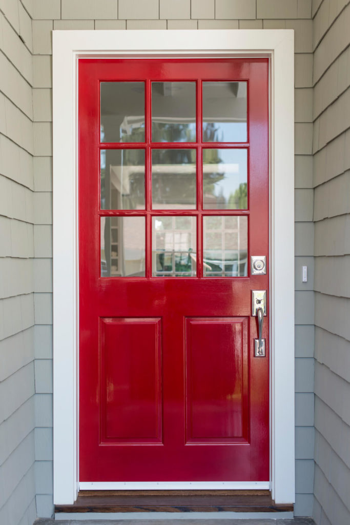 A very simple and contemporary front door with light gray siding and brushed nickel fixtures. The top half of the door is adorned by nine glass panels.