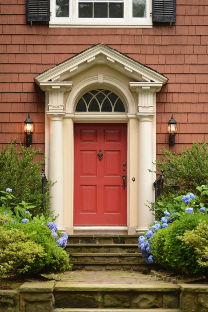 The stone walkway and steps leading up to the bold red front door are lined with shrubbery and bright violet hydrangeas. The siding of the home is in a duller, brick-red.