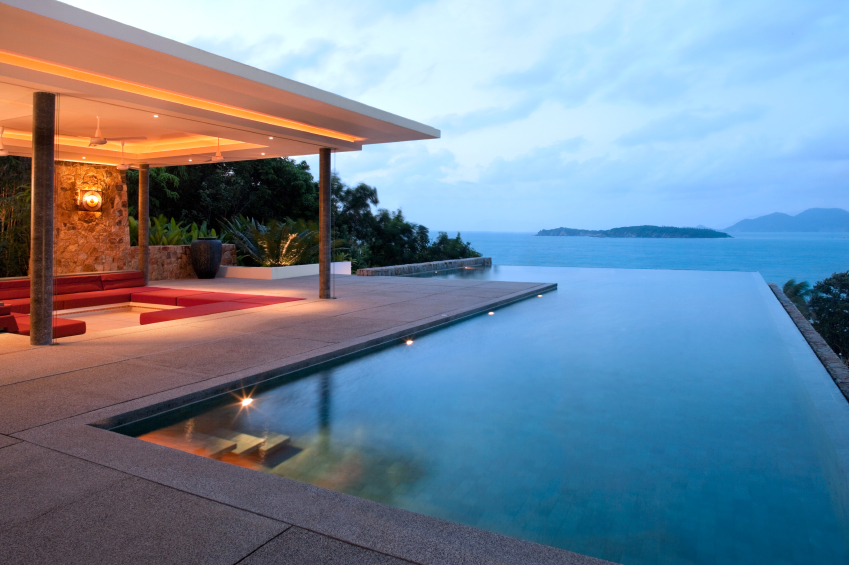 "The infinity pool has stairs leading into it from one corner of the patio. The covered seating area off to the left has a lowered red sectional that extends nearly all the way around the inset. The ""never-ending"" effect of the pool is achieved by positioning the pool facing the open water."