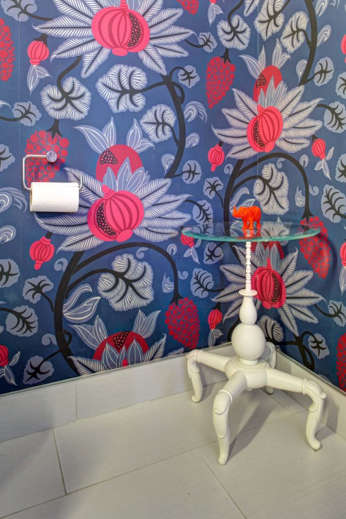 Bathroom features a burst of bright colors, with blue and red floral wallpaper wrapping a white tile floor. Unique white framed, glass-top table stands in corner, holding a single orange rhinoceros sculpture.