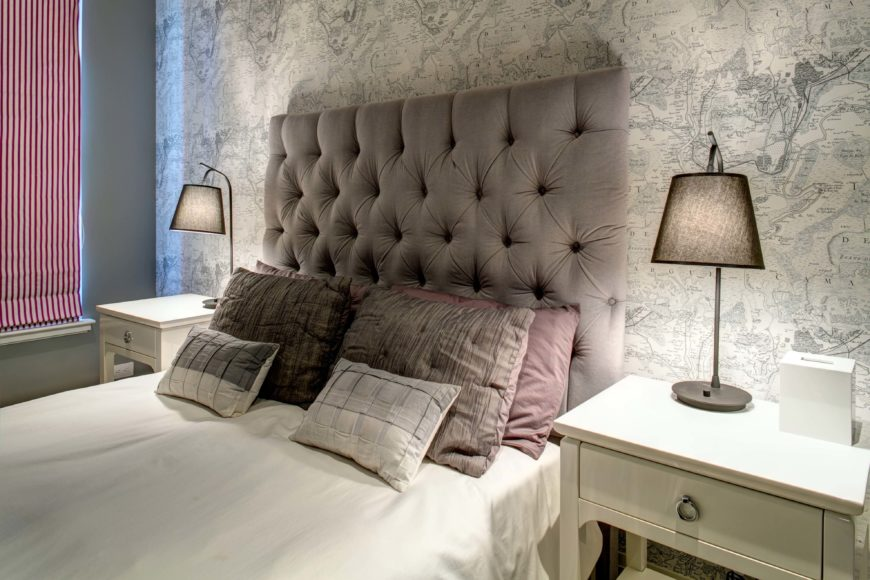 Primary bedroom features an intricate, large scale map all, adding textural detail to the neutral hued space. Large button tufted headboard is flanked by a pair of white bedside tables.
