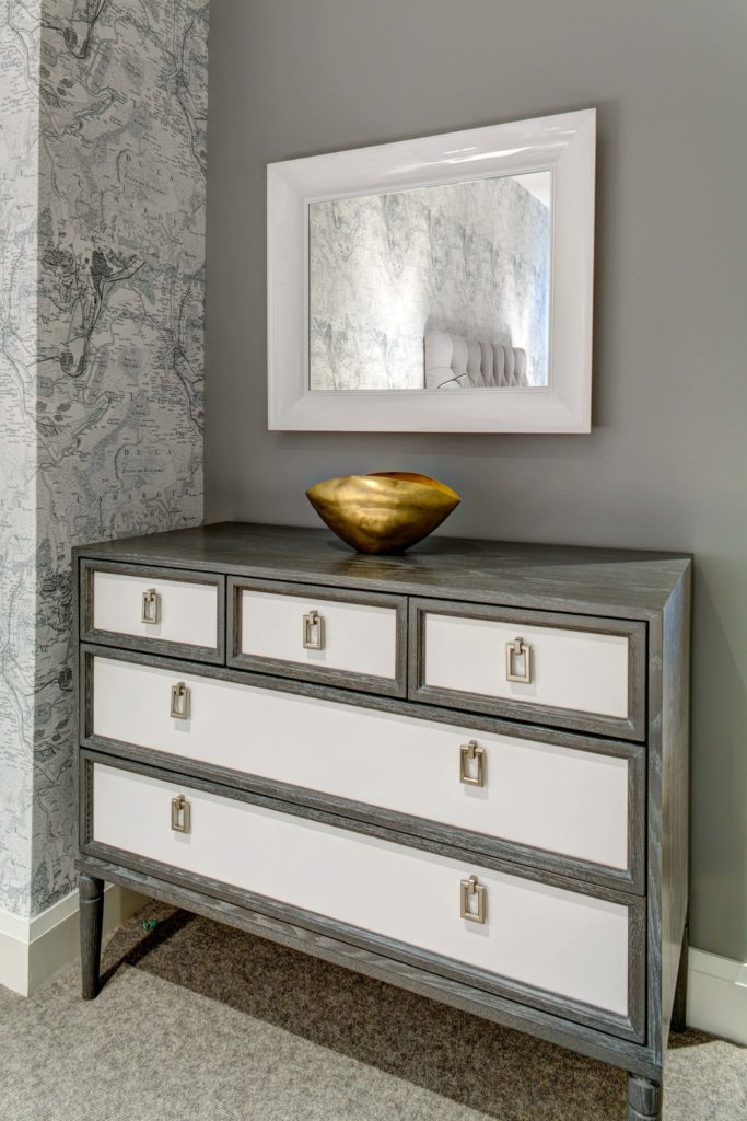 This dresser features a mixture of rustic and contemporary elements, with aged wood framing white drawer panels, and angular metal hardware. The single gold hued bowl standing below white framed mirror injects a burst of color into the space.