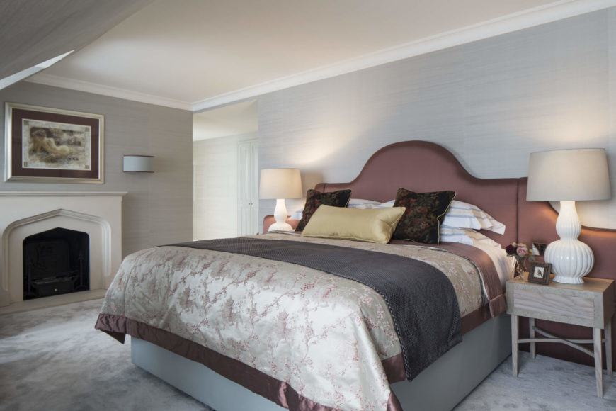 Primary bedroom holds a grandly appointed bed with dark salmon headboard between a pair of natural wood bedside tables, as well as a full fireplace at left.