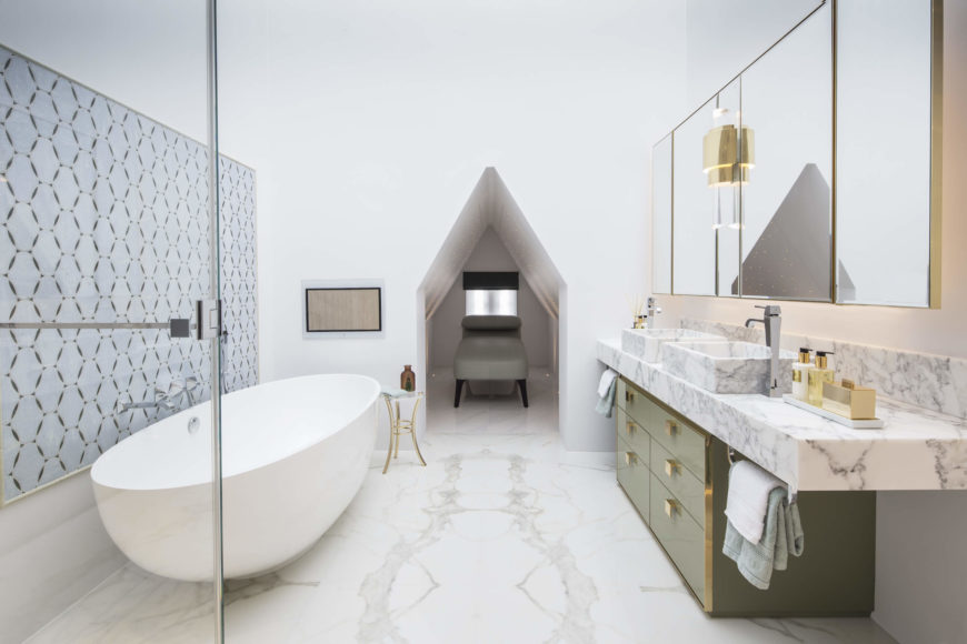 The primary bathroom features a sumptuous mixture of marble and gold detail, within a stark white space. Rounded pedestal tub at left stands across from a dual vanity over green cabinetry, with gold hardware throughout. At center is a small relaxation cubby space.
