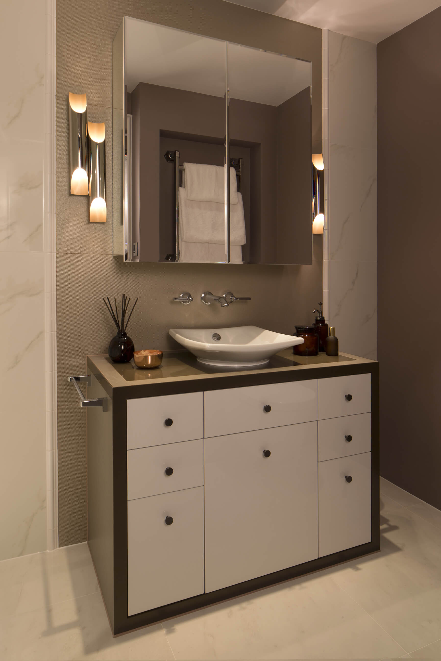 Another bathroom houses this bold, minimalist single vanity, with sleek white cabinetry and white vessel sink, framed in dark tones below a seamless two piece mirror.