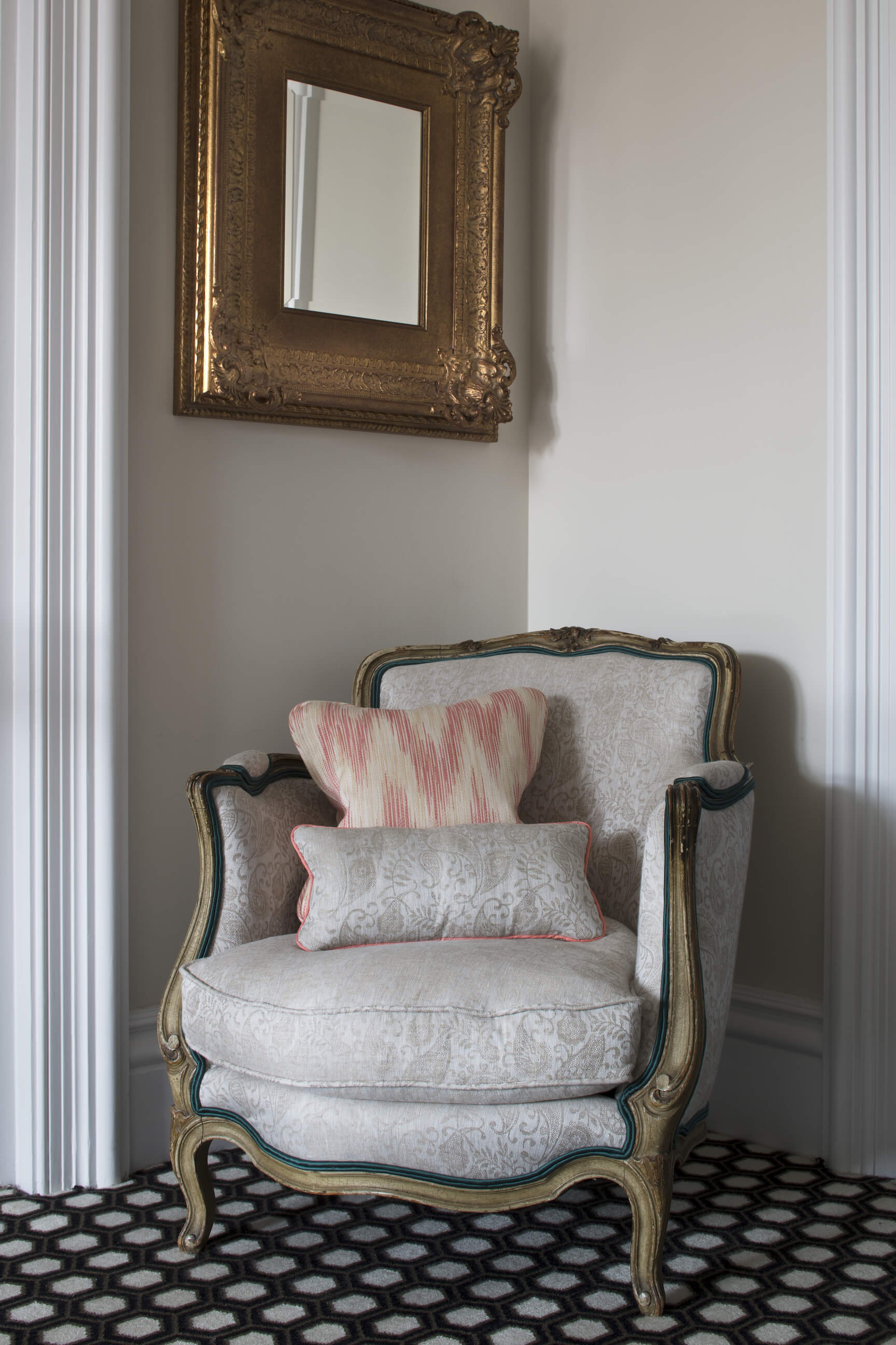 Our final image showcases another ornate corner of the home, featuring this carved wood traditional armchair with floral upholstery, below a richly gold framed mirror.