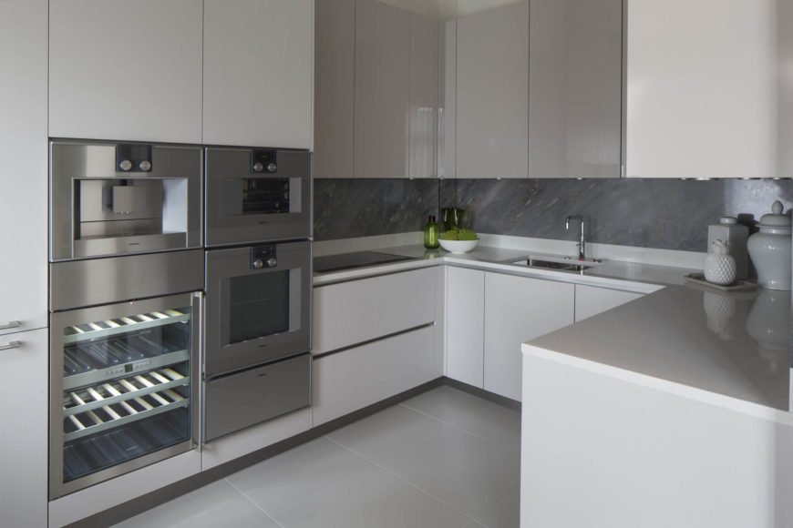 The sleek white countertops are complemented by minimalist cabinetry over the large format tile flooring of the kitchen.