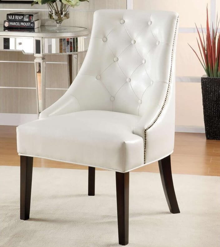 This bespoke white chair features a lightly button tufted backing over thick padded seat cushion. Nail head trim adds contrast to the look, along with dark wood legs.