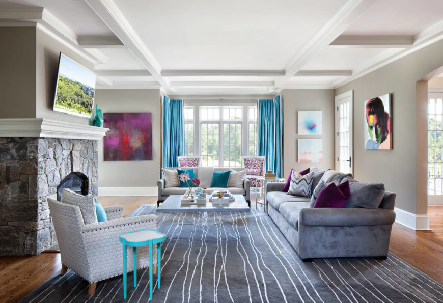 The living room features patterned chairs and a dusky violet sofa in velour. Above the gray stone fireplace is a wall-mounted television. Artwork in the room includes bright modern paintings and a modern interpretation of Elvis. Turquoise and berry accents give this room a real boost of bold color.