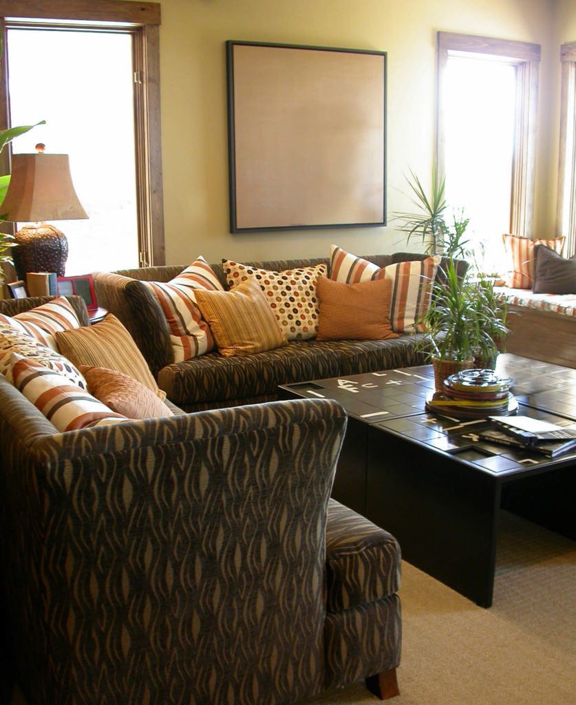 A living room with a unique puzzle coffee table and dark upholstered furniture that contrasts with the light area rug and walls. The pattern of the furniture upholstery is layered against lighter patterned pillows. Visible to the right is a window seat.