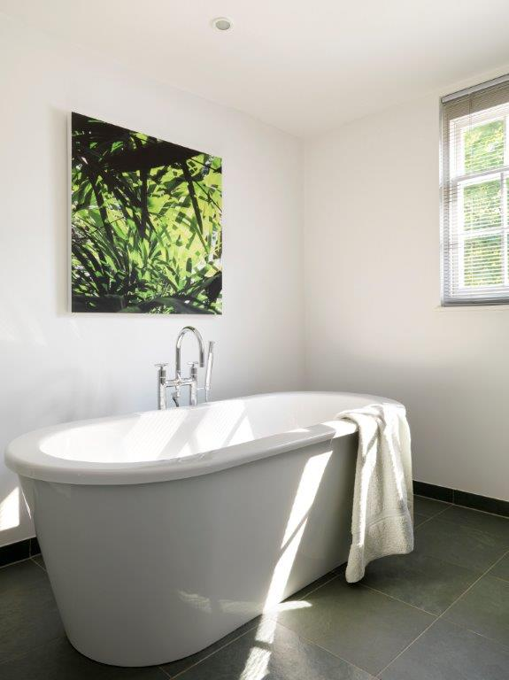 The large, deep, luxurious soaking tub in the primary bathroom, freestanding on dark charcoal tiles. A single painting of lush foliage is on the wall behind the tub.