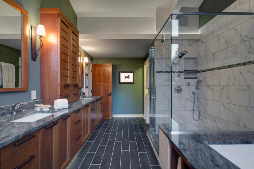 The spacious primary bathroom has gray granite countertops and an enclosed soaking tub. The sinks are separated by custom hardwood cabinetry, with a towel cabinet in between.