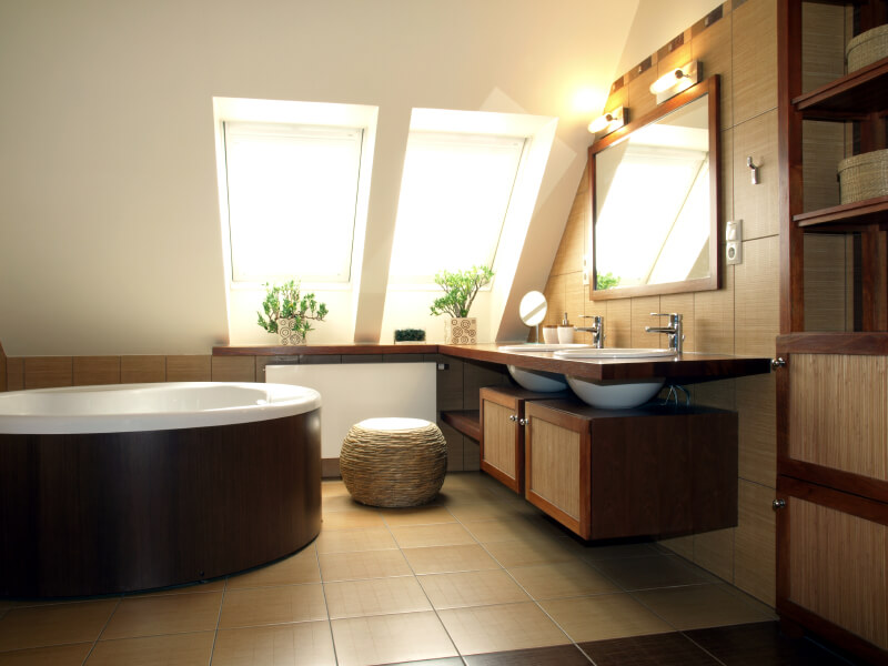 A minimalist bathroom with two skylights above the vanity countertop. Two vessel sinks rest above open-shelving and cabinets. This bathroom is awash in natural fiber and stone for a very Zen atmosphere.