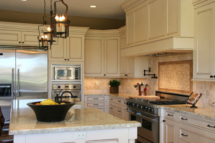A soft stone tile backsplash with a bolder centerpiece behind the stove top. The light backsplash keeps this neutral kitchen in a warm color palette.