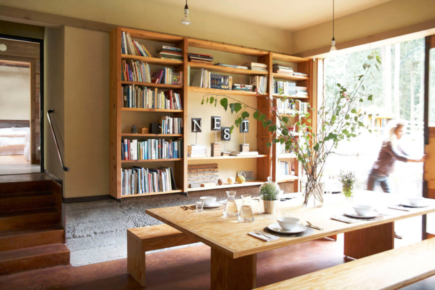 The picnic bench-style dining table is made of reclaimed wood. To the right is a large sliding door that can be opened to let in a cool breeze and plenty of natural light.