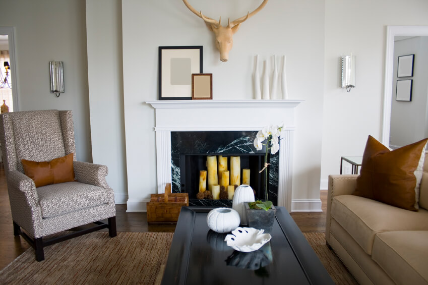 A black marble fireplace filled with pillar candles dominates this small living room. A small mantle keeps the fireplace from overpowering the space. The plaster deer's head mounted above the fireplace is a trendy piece we've been seeing a lot of. Crooked white bottles add character and texture to the mantle.