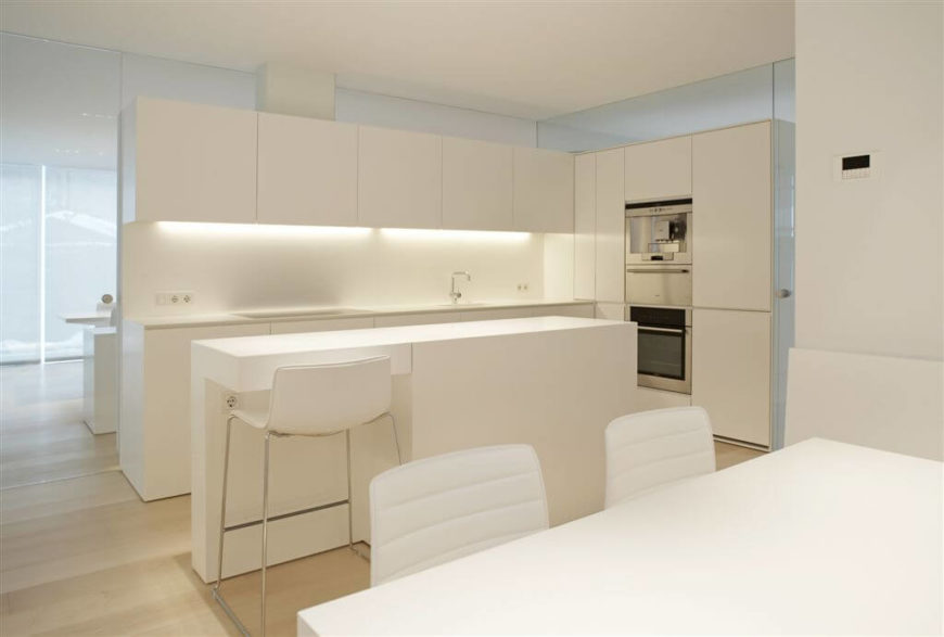 An entire kitchen and dining room in pristine white. The kitchen is divided into two halves by the center wall, with a dining set on either side.