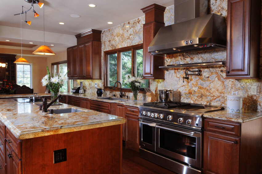 A luxurious rich dark wood kitchen with an enormous amount of marble backsplash with orange veining.