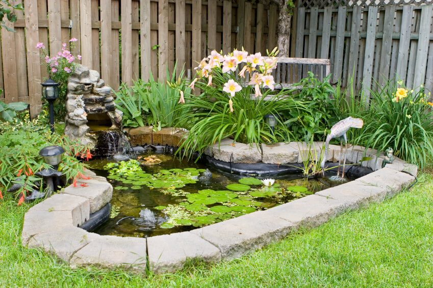 A simple pond edged with stone bricks. At the head of the pond is a small waterfall. Daylilies and other leafy plants surround part of the pond. A metal heron statue stands in the shallows.