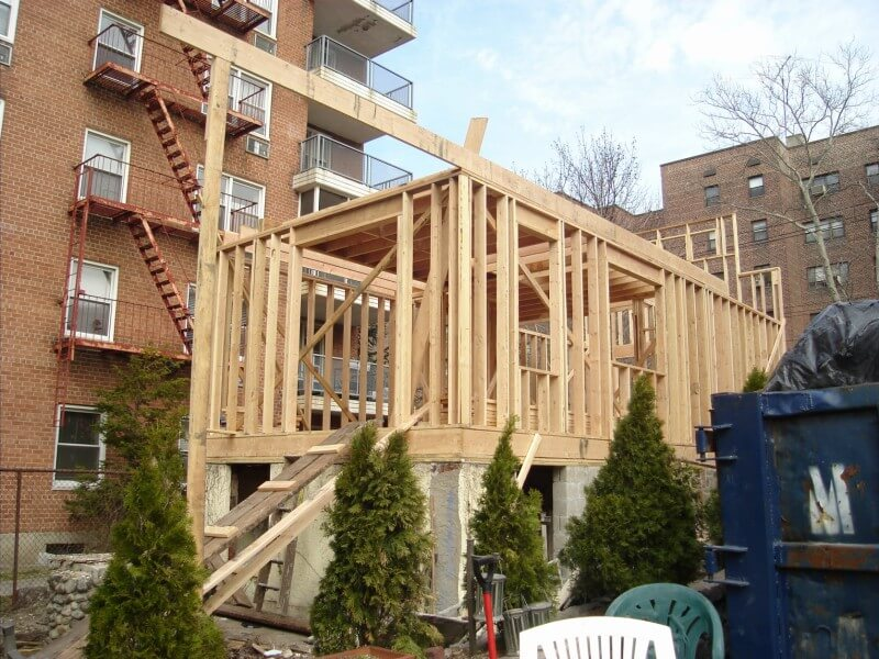 The rear of the home during the framing phase has the same long, box-like shape of the original.