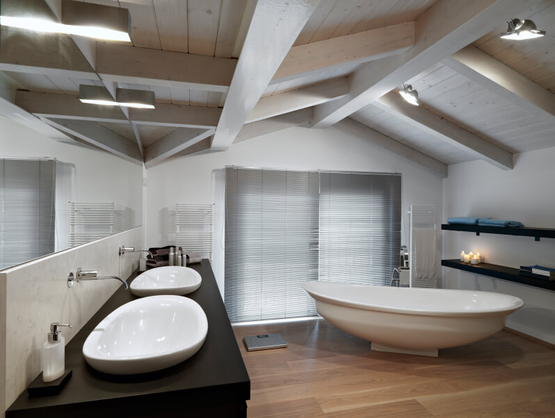 A sleek minimalist attic bathroom with open shelving and boat-like vessel sinks that match the squat free-standing soaking tub. Smooth wall mounted fixtures complete the look.