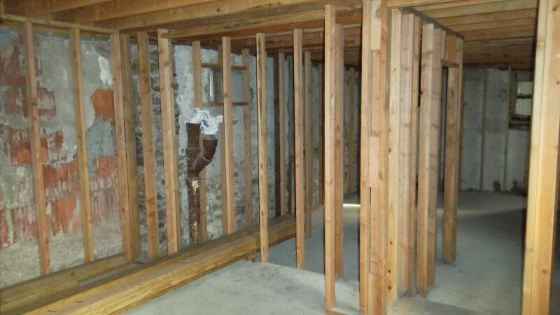 The framed-in basement, with the original foundation and plumbing visible.