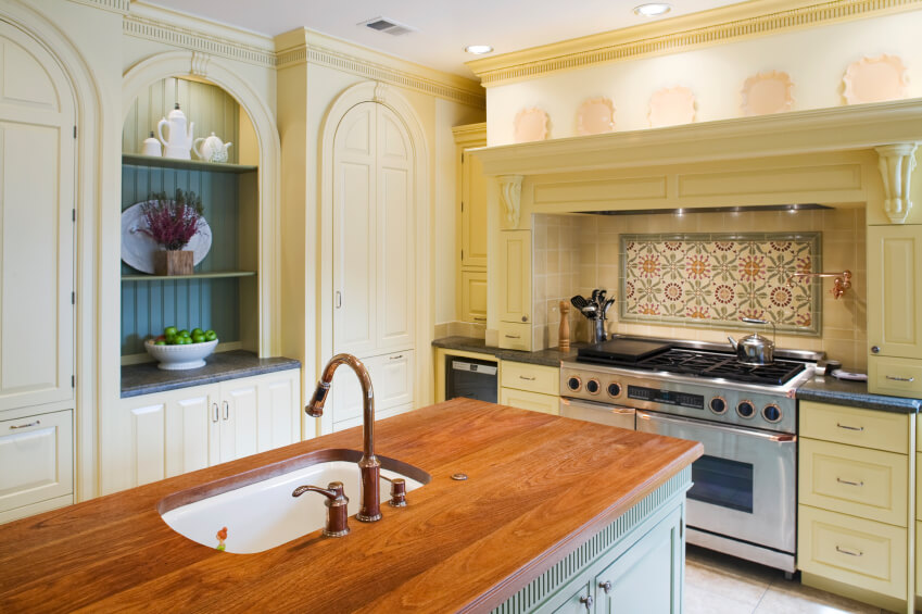 A simple tile backsplash with a kitschy floral pattern as the focal-point behind the range adds additional character to the arched doorways and cabinet openings of this charming kitchen.