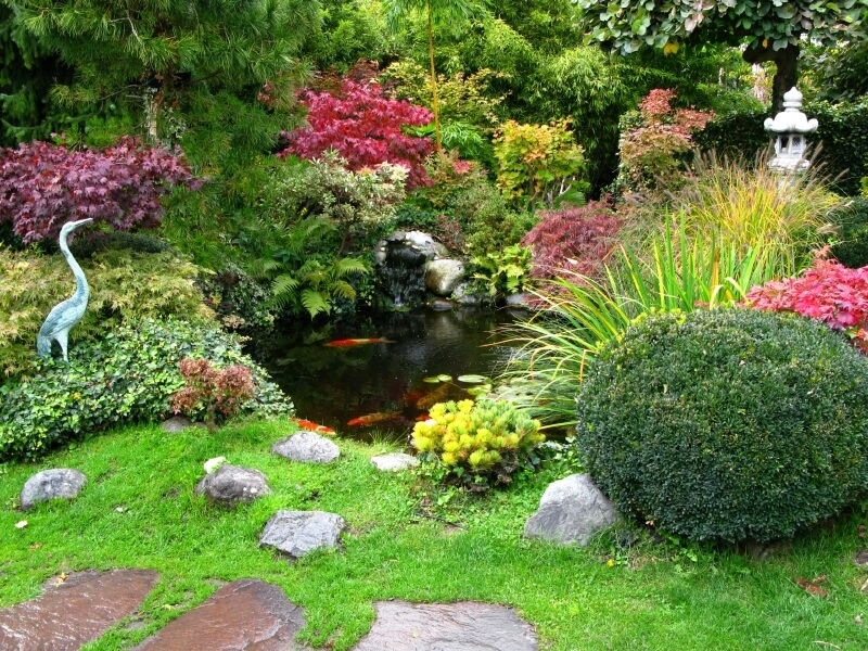 Another view of the Japanese garden with a stone lantern and heron from the pathway. The view changes as visitors walk past the tranquil scene.