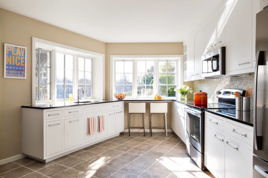 "The airy kitchen is situated in an interesting section of the home that narrows towards the eat-in bar, taking the ""kitchen triangle"" to a whole new level. The high end appliances and white cabinets give this kitchen a bright, shiny, feeling of perfection."