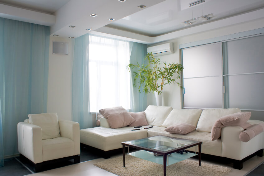 A light and bright pastel living room with a glass-top coffee table. Sheer blue curtains and pale-pink pillows brighten up the white sofa and chair, in addition to the bamboo plant in a tall white vase. Light, airy curtains and a bright color palette keep the dark floors from feeling oppressive.