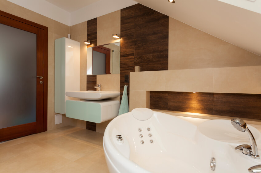 A soaking tub with jacuzzi jets becomes visible from this angle of the previous bathroom. From this angle we can also see the frosted glass wood-framed door and the wooden panelling interspersed with the tile.