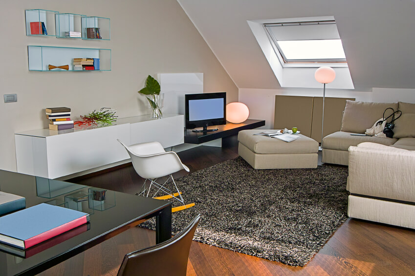 A chic, modern living area with a media center and a table. This space is perfect for a college student's study area.
