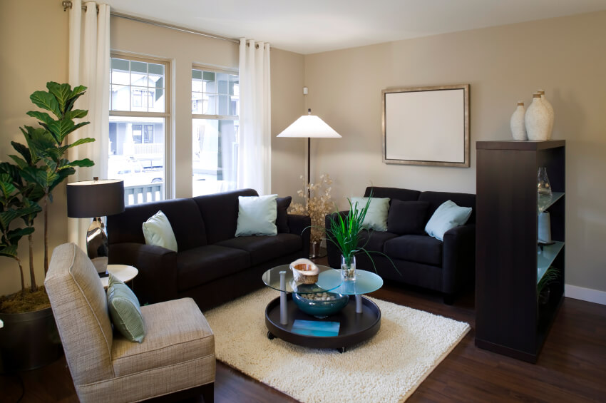 A small living room with an open bookcase acting as a room barrier in the open-concept main floor. The sofas and chair are arranged around a multi-tier coffee table on a small, but plush, area rug. Accents in this room include jute-wrapped pottery, small houseplants, and a water feature on the bottom of the coffee table.
