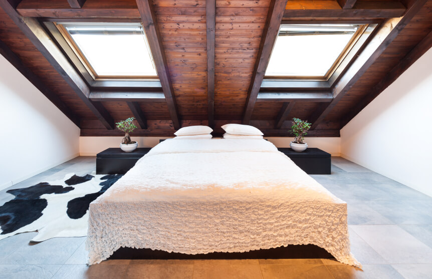 Dark stained wood, cowhide, and a ruffled bedspread create a contrast of masculine and feminine styles. Bonsai trees on either side of the low profile bed frame add Asian flair to the design as well.