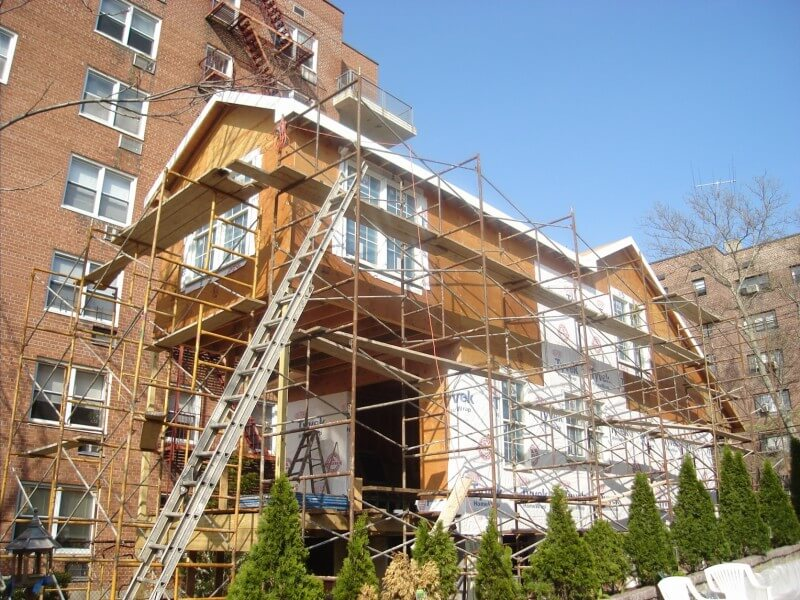 This image highlights the extensive scaffolding used while installing the siding and windows.