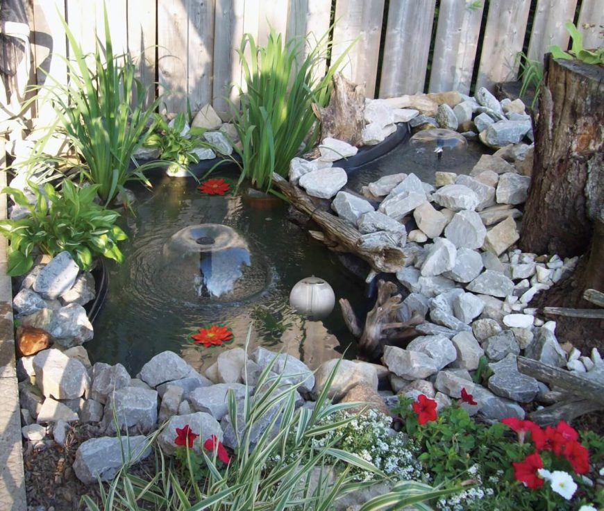 A small two-section pond with a waterfall between the two. Both sections have small umbrella fountains. The entire pond is edged by stacked stones that help hide the black liner. Petunias, hostas, and lilies are planted around the outside of the pond, with a few water lilies on the surface.