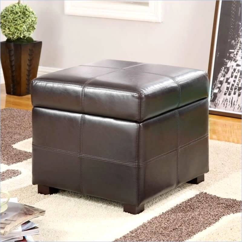 This cubic dark coffee leather ottoman is crossed with stitching for textural interest. The thick cushioned top hides a large storage space.
