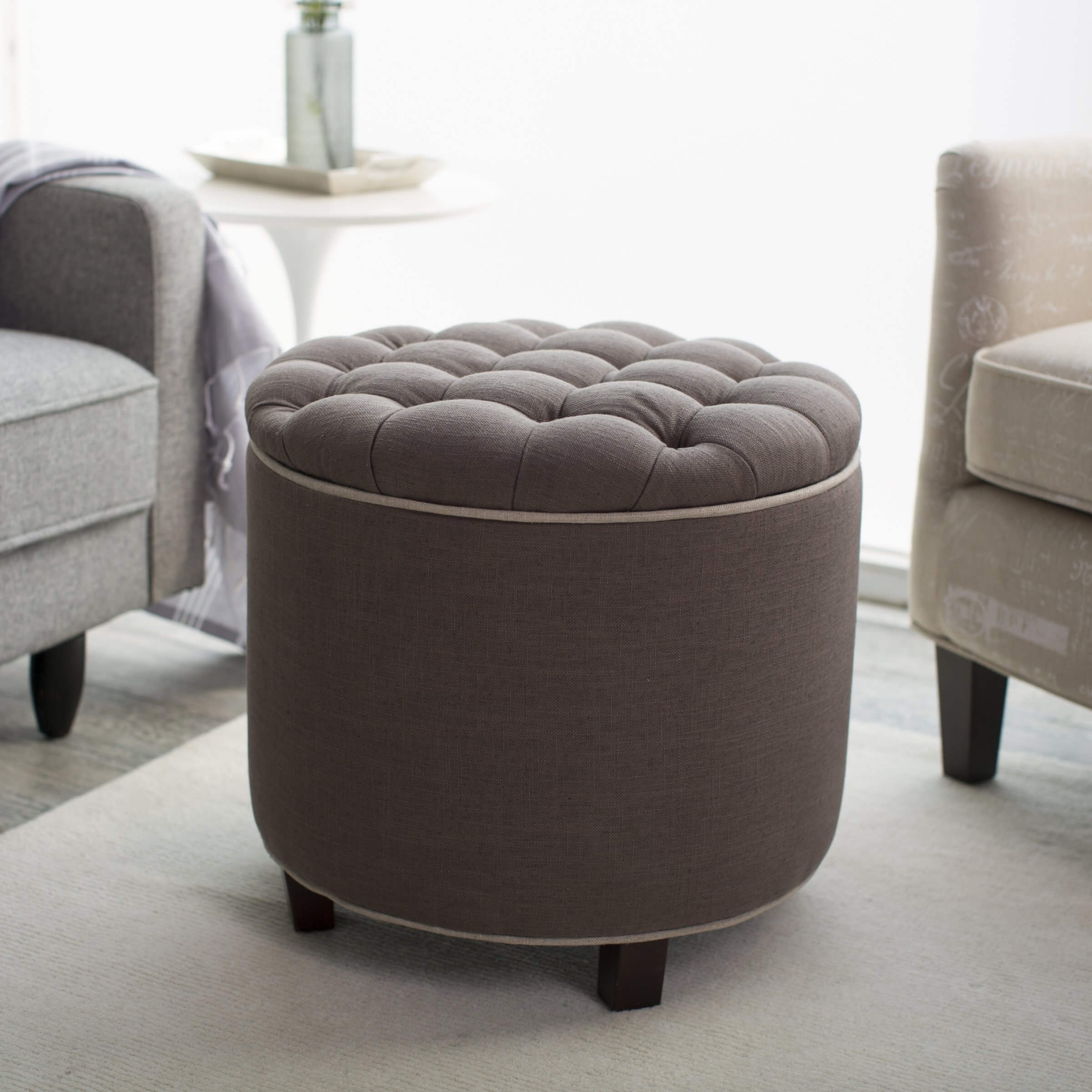 Here's a taller, round ottoman with light chocolate tufted upholstery, standing mildly apart from the light hues of the surrounding room.