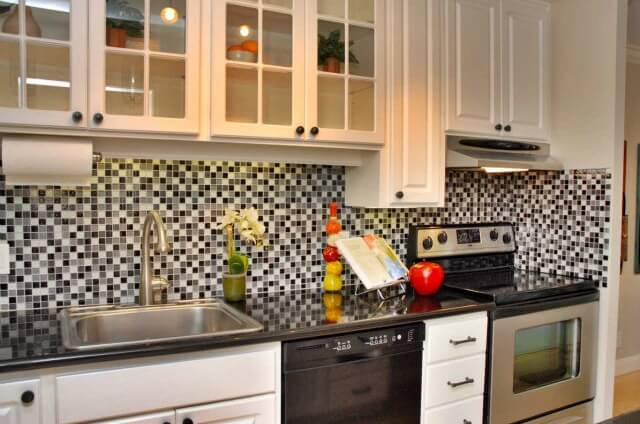 A white kitchen with glass-faced cabinets above the main preparation area and sink. The backsplash is a mix of black, gray, and white glass mosiac tiles.