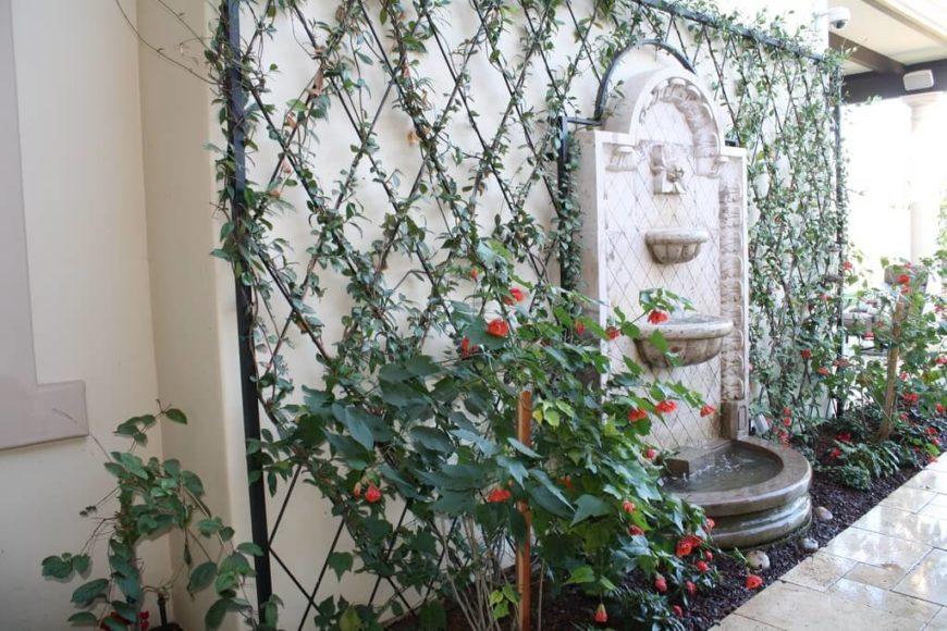A diamond-patterned lattice surrounds a wall fountain.