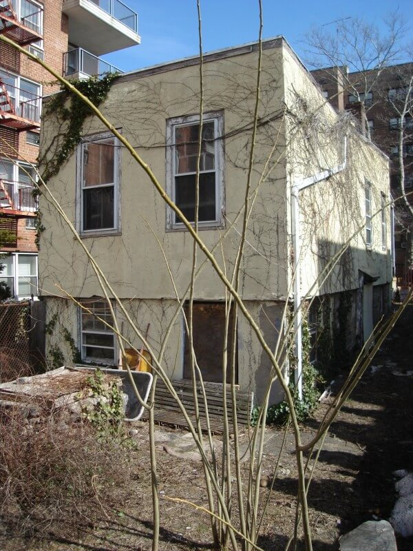"""The rear of the square """"cracker-box"""" home had a strange shifted second level and a backyard strewn with debris and dead grass. The windows were broken or boarded up. The rear of the home was also covered in skeletal dead vines."""