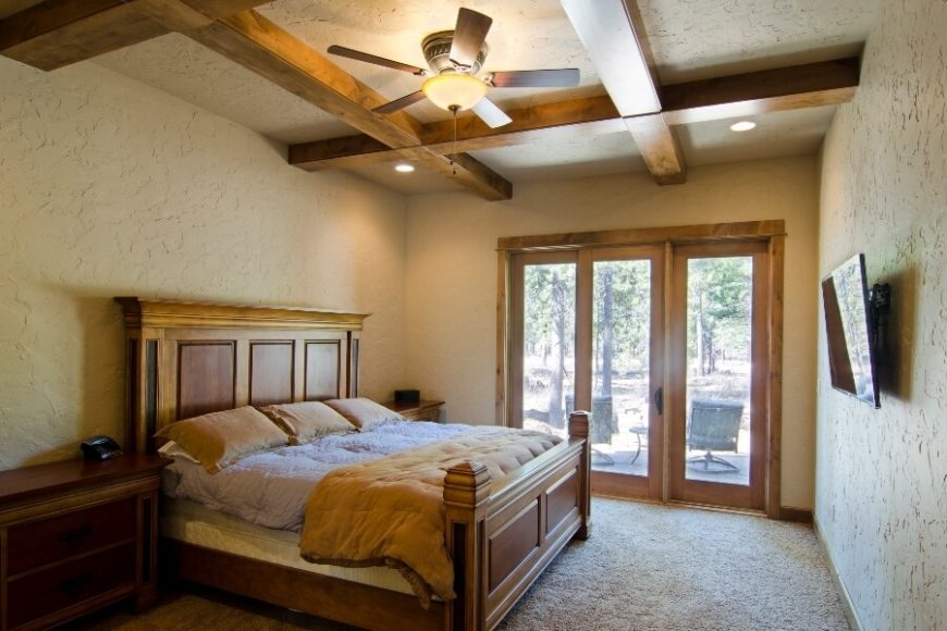 One of the main floor bedrooms with plaster walls and extensive woodwork that includes a wooden coffered ceiling. The carved details of the bed with black and red inlays give this room a rustic, southwestern atmosphere. A glass-paneled door with two sidelights opens up to the backyard.
