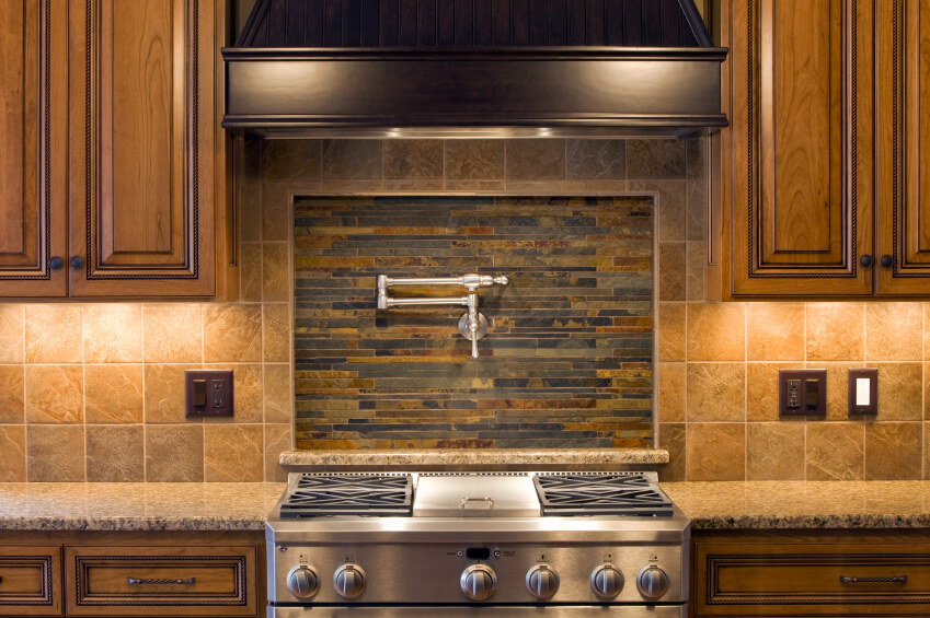 A beautiful kitchen in shades of brown with a stone backsplash and an inset center focal point of thin, long tiles of charcoal and bronze.
